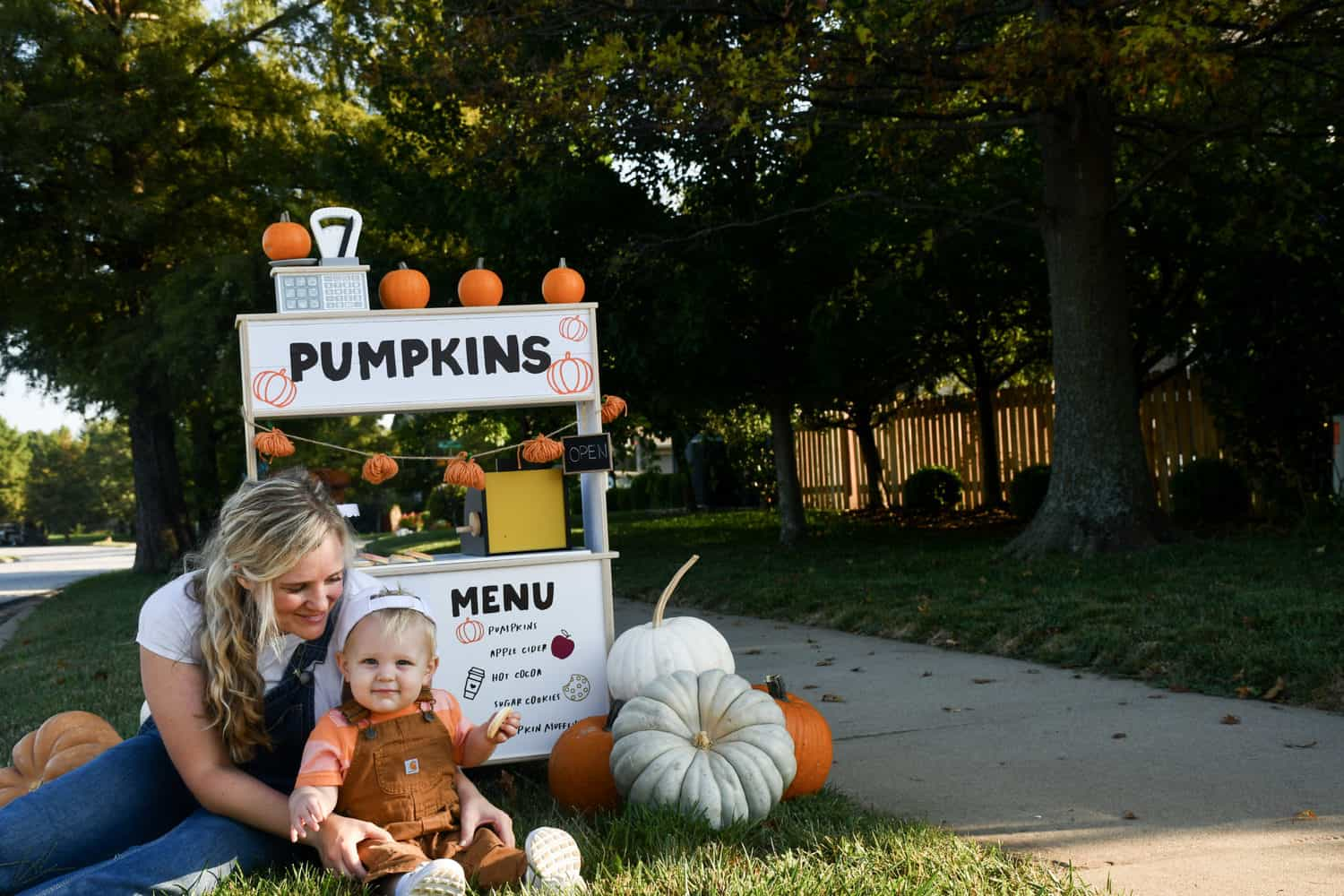 Mom and child sitting in front of pumpkin stand.