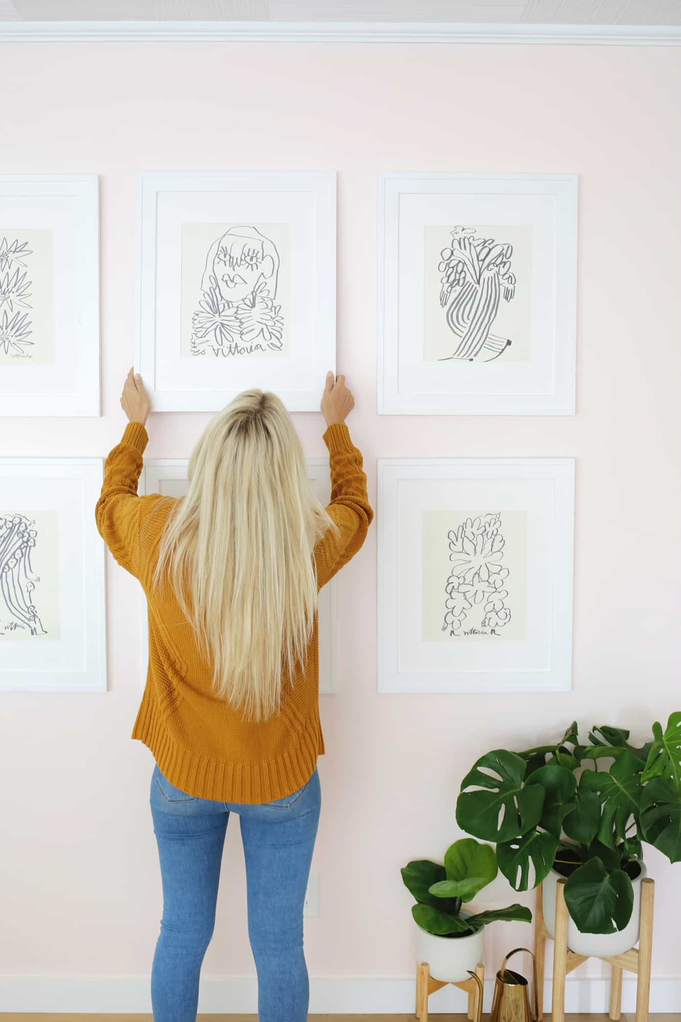 woman hanging a print on a gallery wall