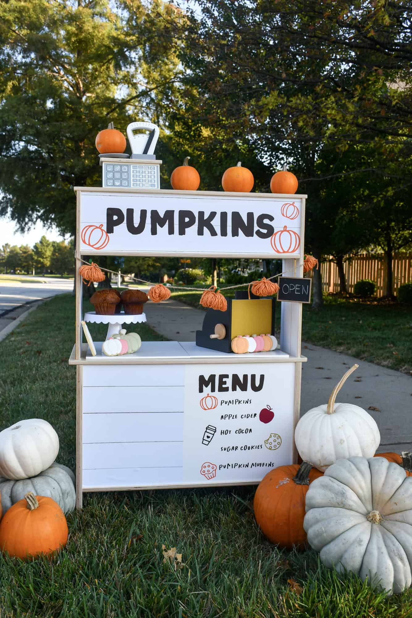 Decorated pumpkin stand made from the Ikea play kitchen. Has toys on it and pumpkins around it.