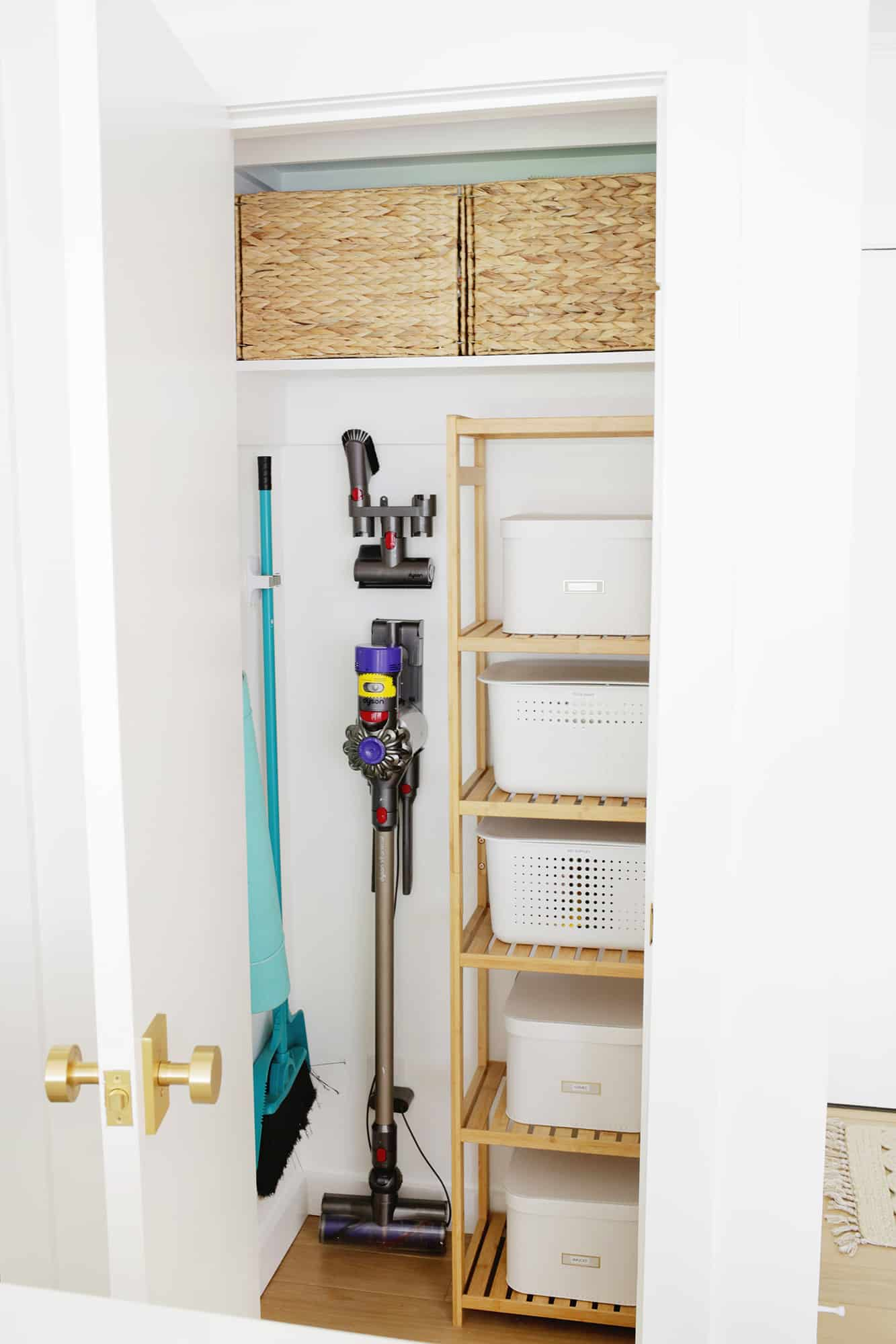 Organized closet with hanging cleaning items and baskets