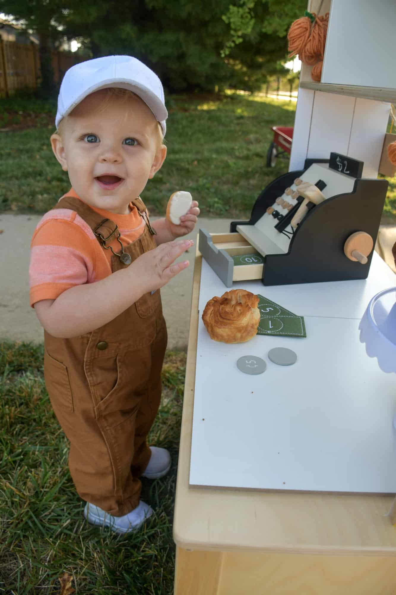Child holding a cookie and playing with a toy cash register.