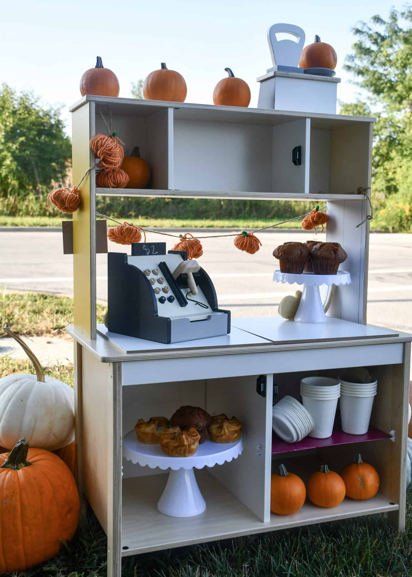 Inside of pumpkin stand, can see the treats, back of cash register, cups and pumpkins.
