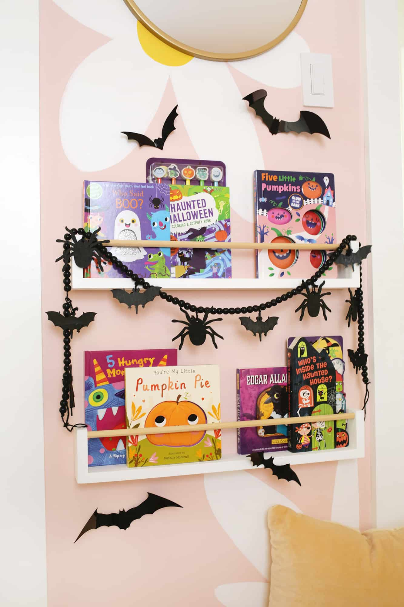 bookcase with halloween books on it and halloween decorations around it