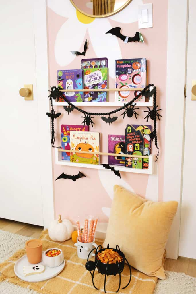 halloween decorated bookshelf with snacks, a blanket, and pillow underneath