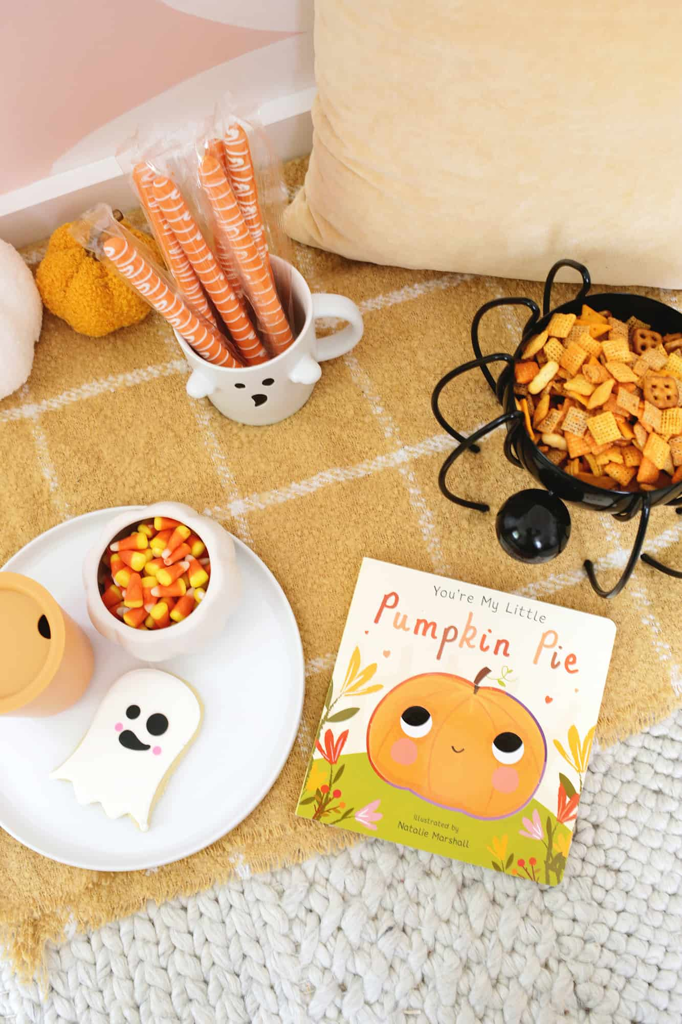 book with a pumpkin on it sitting by snacks on a blanket
