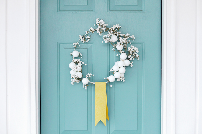 Make this simple white winter wreath with a coat hanger and ping pong balls!